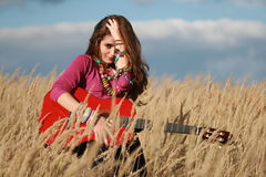 Girl holding guitar and fixing hair in field. Young country woman fixing hair and holding a guitar in field against blue cloudy sky backgrund Royalty Free Stock Image