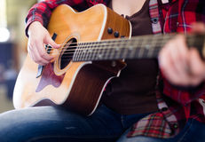 Girl holding guitar. Focus on strings of guitar Royalty Free Stock Images