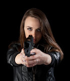 Girl holding gun. Shot of a beautiful girl holding gun, isolated on black background royalty free stock photo