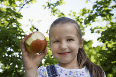 Girl Holding Half Eaten Apple Outdoors Stock Photo