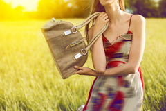 Girl holding hand bag outdoors on the nature at sunset time Stock Photography