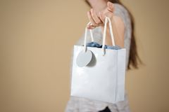Girl holding in hand blank blue paper gift bag mock up. Empty pa royalty free stock image