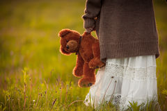 Girl holding in hand brown teddy bear on morning field. Girl holding in her hand brown teddy bear Royalty Free Stock Photos