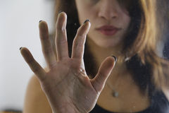 Girl holding hand on door glass Stock Images