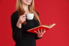 A girl holding in a hand an open book and a cup with a drink and smiling . Red background. Close-up. stock images