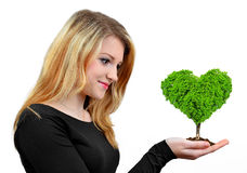 Girl holding in hand  tree. In the shape heart isolated on white Stock Image