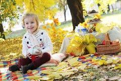 Girl holding handmade pumpkin under autumn tree Royalty Free Stock Images