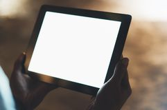 Girl holding in hands on blank screen tablet on background illumination glow bokeh light in night atmospheric city, hands using. Template mobile computer on stock images