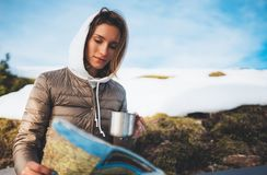 Girl holding in hands cup of drinks, tourist look on map, people planning trip in snow mountain, hipster on background winter royalty free stock photo
