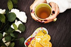 Girl holding hands with a Cup of green tea on the table with the white flowers. The girl holds a Cup of tea on a plate of cookies and lit a white flowers royalty free stock image