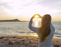 Girl holding hands in heart shape at beach. Blonde young girl holding hands in heart shape framing setting sun at sunset on ocean beach Stock Photo