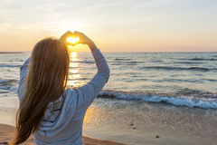 Girl holding hands in heart shape at beach. Blonde young girl holding hands in heart shape framing setting sun at sunset on ocean beach Royalty Free Stock Photography