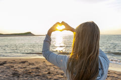 Girl holding hands in heart shape at beach. Blonde young girl holding hands in heart shape framing setting sun at sunset on ocean beach Royalty Free Stock Images