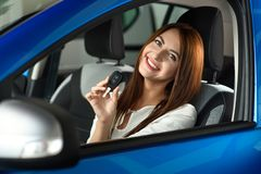 Girl holding in hands keys from new car stock photo