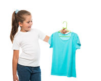 Girl holding hanger with turquoise t-shirt Stock Images