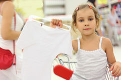Girl holding hanger with white shirt Stock Image
