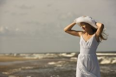 Girl holding hat at beach. Stock Photography