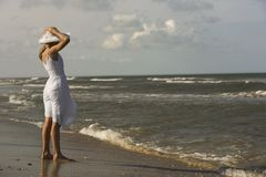 Girl holding hat on head at the beach. royalty free stock photos