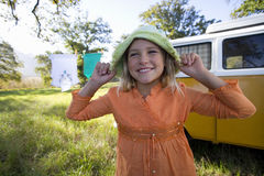 Girl (9-11) holding hat on head by camper van in field, smiling, close-up Royalty Free Stock Image