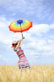 Girl holding hat rising umbrella and standing in Stock Photos