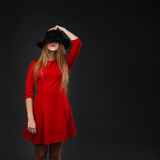 Girl holding hat up to face Stock Photo