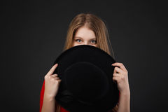 Girl holding hat up to face Royalty Free Stock Photos