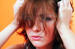 Girl Holding Head. Young teenage girl with an expression holding the side of her head with her hands Stock Photography