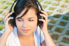 Girl holding headphones and listening to music. Outside in park with copy text space Stock Photo