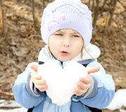 Girl holding heart. Girl holding  heart fashioned out of snow Royalty Free Stock Photography