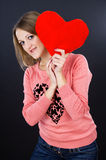 Girl holding a heart on a black background Stock Images