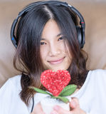 Girl is holding heart love flower while listen to music Stock Photos