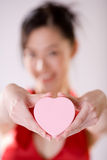Girl holding heart shape box. Beautiful out of focus smiling girl holding a pink heart shape valentine box Royalty Free Stock Photography
