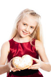 Girl holding a heart-shaped biscuit Royalty Free Stock Photography