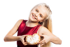 Girl holding a heart-shaped biscuit Stock Photo