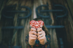 Girl holding a heart shaped decorated gingerbread, Royalty Free Stock Photography