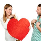 Girl holding heart symbol pointing at boy. Stock Photos