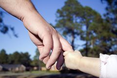 Girl holding her father's hand. Little girl holding her daddy's hand Royalty Free Stock Photo