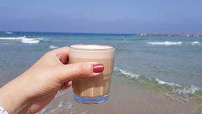 Girl holding in her hand latte coffee in transparent glass against sea waters. At background royalty free stock photos