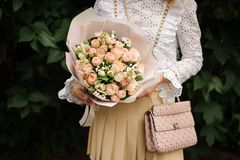 Girl holding bouquet of champagne color roses. Girl holding in her hands a beautiful bouquet of champagne color roses in the gift paper in the park stock photos