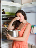 Girl holding her nose because of bad smell. From food near refrigerator at home stock images