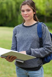 Girl holding her notebook while carrying her backp Stock Images