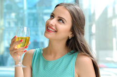 Girl holding in her right hand a full glass of white wine Stock Photo