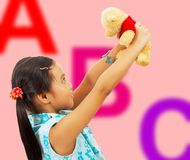 Girl Holding Her Teddy Bear Up In The Air Royalty Free Stock Images
