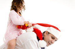 Girl holding her toy riding on her father's back Stock Image