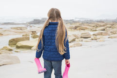 Girl holding her wellington boots at beach Royalty Free Stock Photo