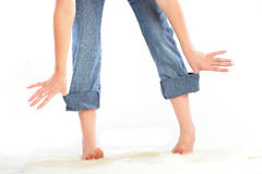 Girl holding herself for rolled up jeans. Stock Photography