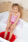 Girl holding his feet in cold water. Harden Stock Photos