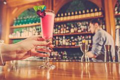 The girl is holding in his hand a glass of alcoholic beverage. At bar stock photo