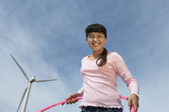 Girl Holding Hula Hoop At Wind Farm Royalty Free Stock Photo