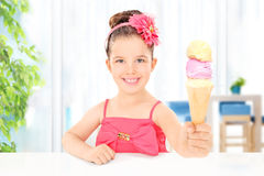 Girl holding ice cream sitting in the living room Stock Images